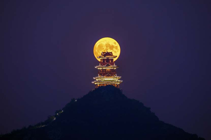 The moon is seen behind the Dingdu Pavilion on the evening of Mid-Autumn Festival, Beijing, Oct. 1, 2020. Wu Luping/People Visual
