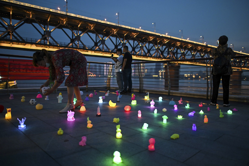 A woman sets out light-up toys along the Yangtze River in Wuhan, Hubei province, Sept. 24, 2020. Hector Retamal via People Visual