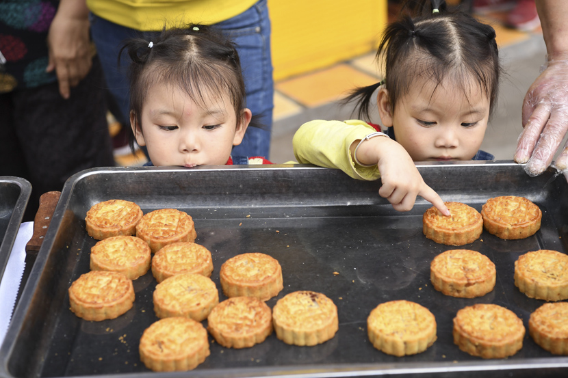 Twin girls pick out their favorite mooncakes ahead of the Mid-Autumn Festival in Chongqing, Sept. 26, 2020. Chen Chao/CNS/People Visual