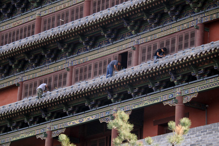 Workers add Ming and Qing Dynasty-style features to a building in Datong, Shanxi province, June 14, 2017. Chen Xiaodong/IC