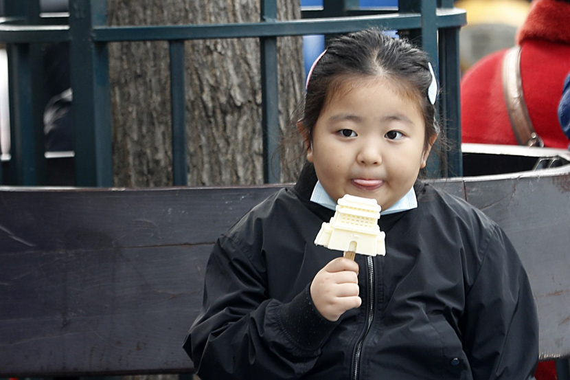 A girl enjoys a popsicle in Beijing, Oct. 8, 2020. Han Haidan/CNS/People Visual