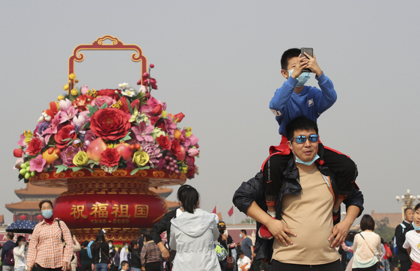 A boy takes photos from his father's shoulders in Tiananmen Square, Beijing, Oct. 7, 2020. IC