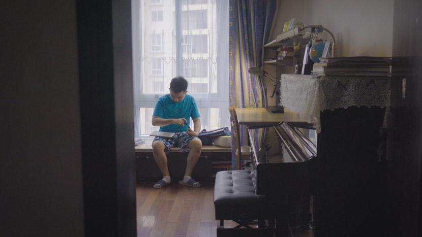 Cai Lechen plays with his iPad at home in Shanghai, September 2020. Zhu Jiaqi for Sixth Tone