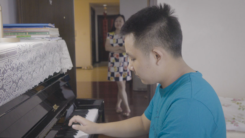 Cai Lechen plays piano at home, while his mother Mei Li watches, in Shanghai, September 2020. Zhu Jiaqi for Sixth Tone