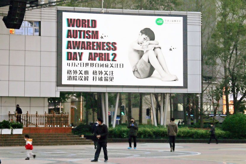 People walk past a poster promoting public awareness of autism, in Shanghai, April 1, 2020. People Visual