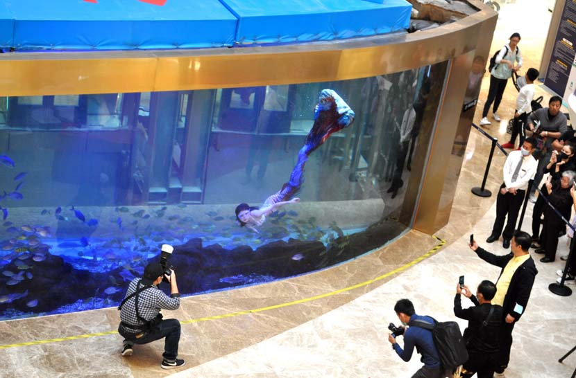 """Photographers capture a """"mermaid"""" in a shopping mall in Shanghai, Oct. 17, 2020. The shopping mall held its first mermaid competition, attracting more than 30 participants. People Visual"""