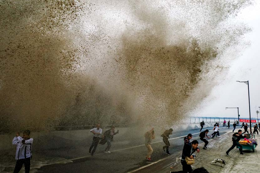 People flee from a huge wave along the Qiantang River, Oct. 18, 2020. People Visual