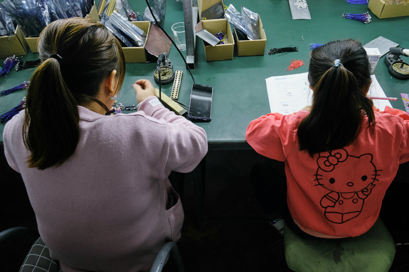 Luo Ruihong works at a community factory while her daughter does homework next to her, in Lüeyang County, Shaanxi province, Sept. 26, 2020. Wu Huiyuan/Sixth Tone
