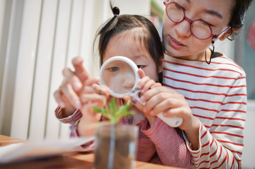 A mother teaches her daughter how to observe plants at home in Beijing, March 17, 2019. Mai Tian/People Visual