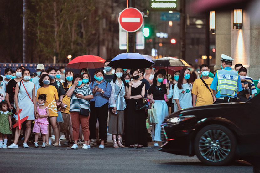 People wearing masks wait to cross the street in Shanghai, June 19, 2020. Jiang Zhenyao/People Visual