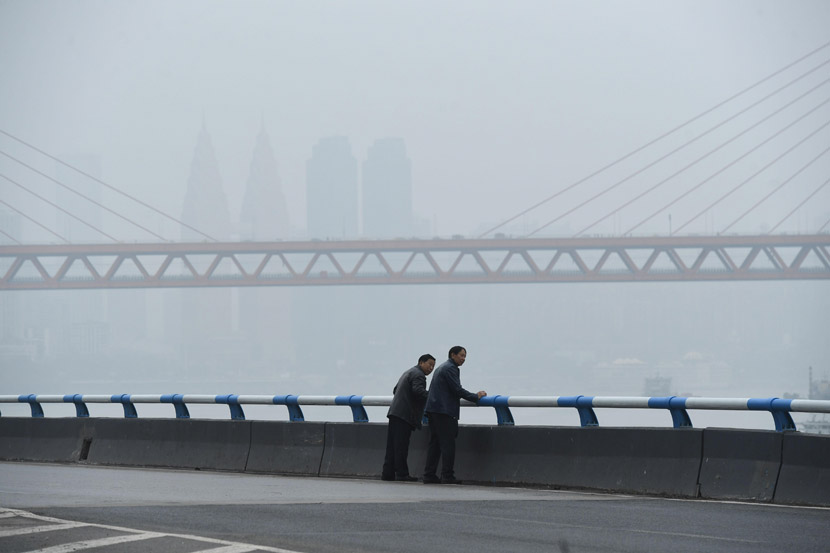 Two men stand on a bridge during a foggy day in Chongqing, Oct. 19, 2020. Chen Chao/CNS/People Visual