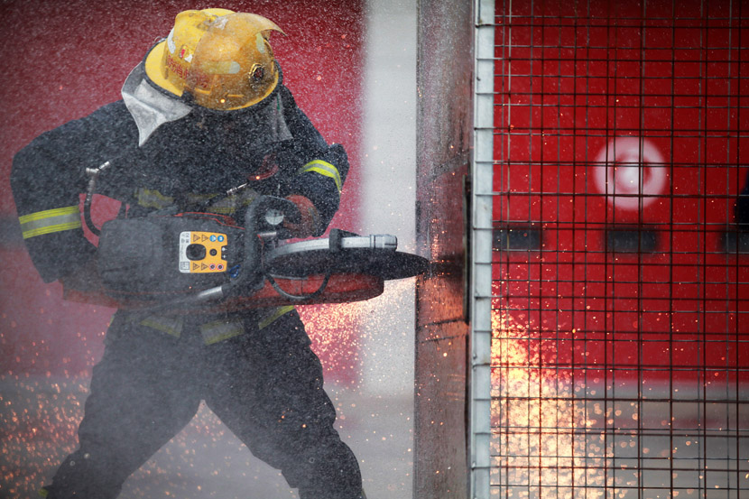 A firefighter cuts a steel plate during a drill in Yangzhou, Jiangsu province, Oct. 21, 2020. Meng Delong/People Visual