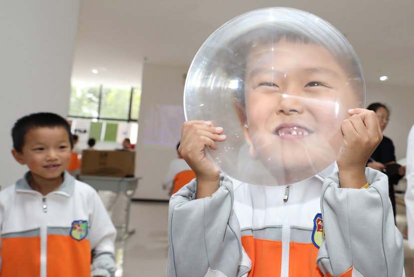 A pupil holds a magnifying lens at a primary school in Xi'an, Shaanxi province, Oct. 20, 2020. IC