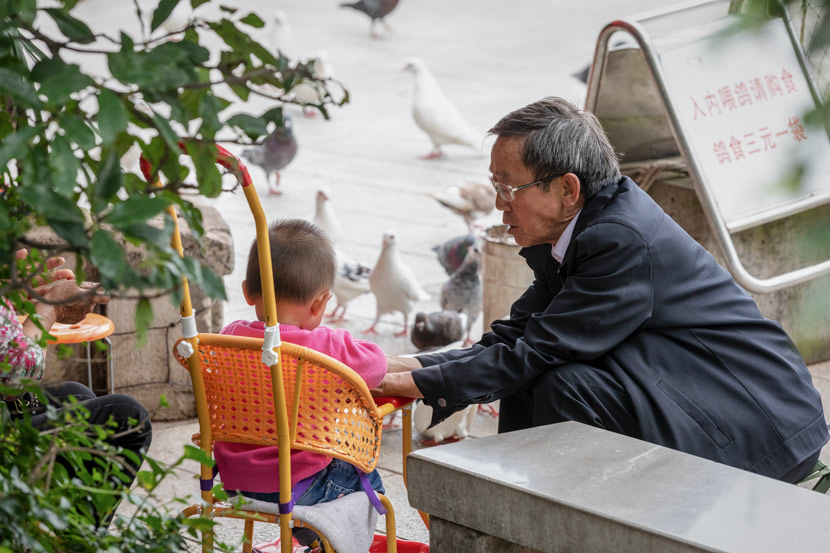 An elderly resident takes care of a child at a park in Qujing, Yunnan province, May 31, 2018. Wan Huizhou/People Visual
