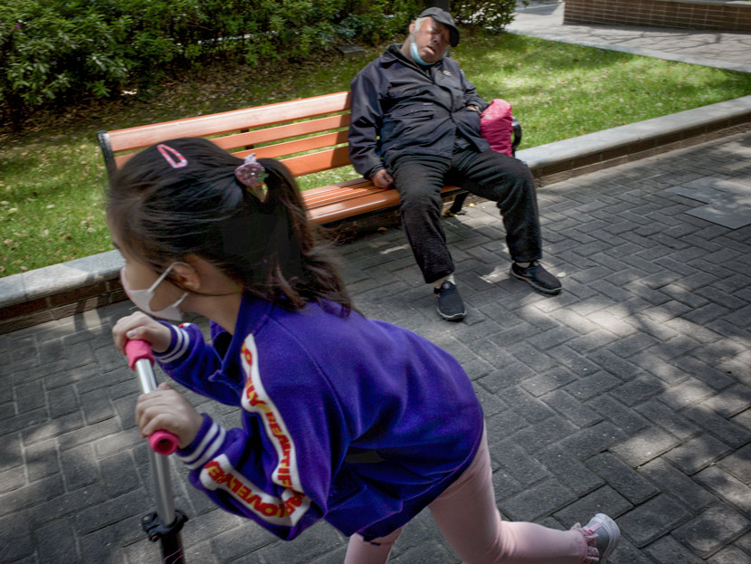 A girl plays on a scooter, while an elderly man takes a nap on a bench, in Shanghai, April 29, 2020. Zhang Yan/People Visual