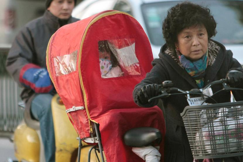 A woman takes her grandchild home by bike in Nanjing, Jiangsu procince, Dec. 7, 2010. An Xin/People Visual