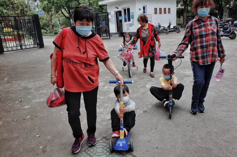 Seniors take their grandchildren home after a visit to a park in Shanghai, May 14, 2020. People Visual
