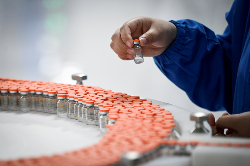 A staff member works on the production line for Sinovac's COVID-19 vaccine in Beijing, Sept. 24, 2020. People Visual