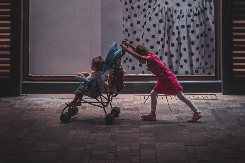 A girl pushes a toddler in a stroller, in Beijing, 2018. Zhang Chi/People Visual