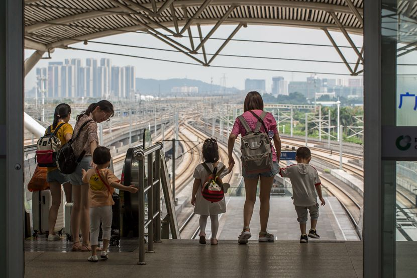 Parents and their children get ready to board a train at a railway station in Guangzhou, Guangdong province, July 1, 2019. Liang Weipei/Southern Metropolis Daily/People Visual