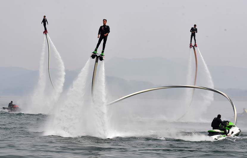 Tourists play on water jetpacks on Dongjiang Lake in Zixing, Hunan province, Oct. 31. Guo Liliang/People Visual