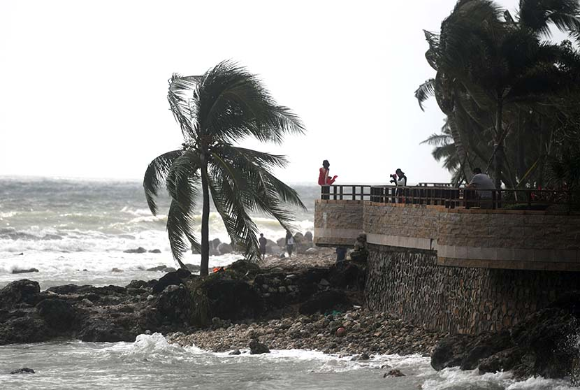 A woman is photographed by the sea on a windy day as Typhoon Goni approaches the South China Sea, Sanya, Hainan province, Oct. 29, 2020. People Visual