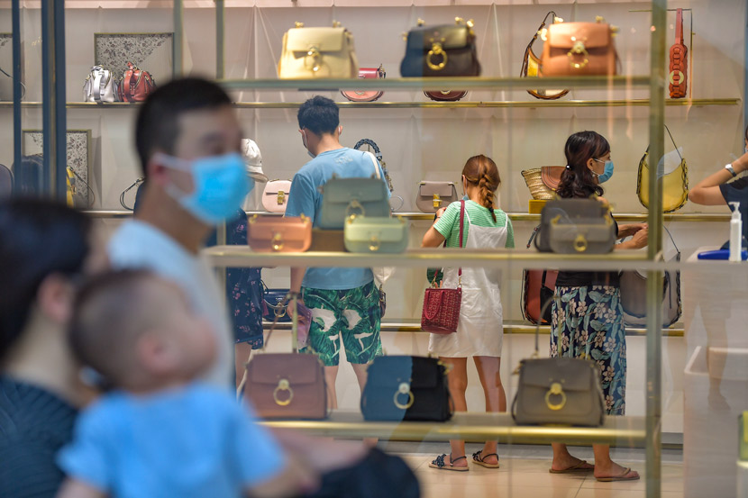People look at handbags at a duty-free shop in Sanya, Hainan province, Oct. 2, 2020. Luo Yunfei/CNS/People Visual