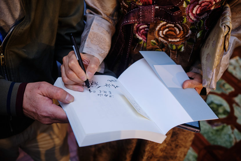 """A woman signs her name in a copy of """"Friends in Need Are Friends Indeed"""" at the third annual China International Import Expo in Shanghai, Nov. 6, 2020. Wu Huiyuan/Sixth Tone"""