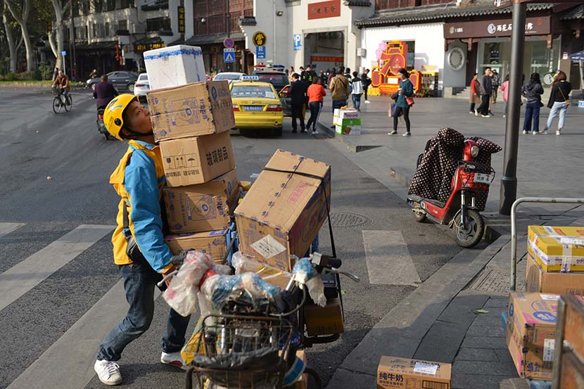 A delivery worker carries packages in Nanjing, Jiangsu province, Nov. 13, 2020. People Visual