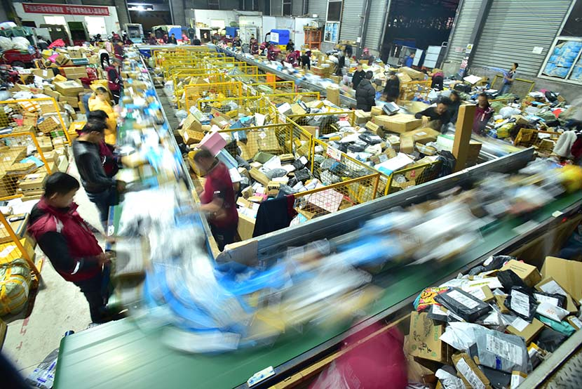 Workers sort parcels at a distribution center in Neijiang, Sichuan province, Nov. 16, 2018. People Visual