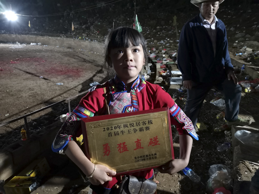 "A girl in traditional Sani Yi dress dispays a plaque honoring the owner of the event's best ""charging bull"" after a bullfight event in Shilin Yi Autonomous County, Yunnan province, October 2020. Kenrick Davis/Sixth Tone"