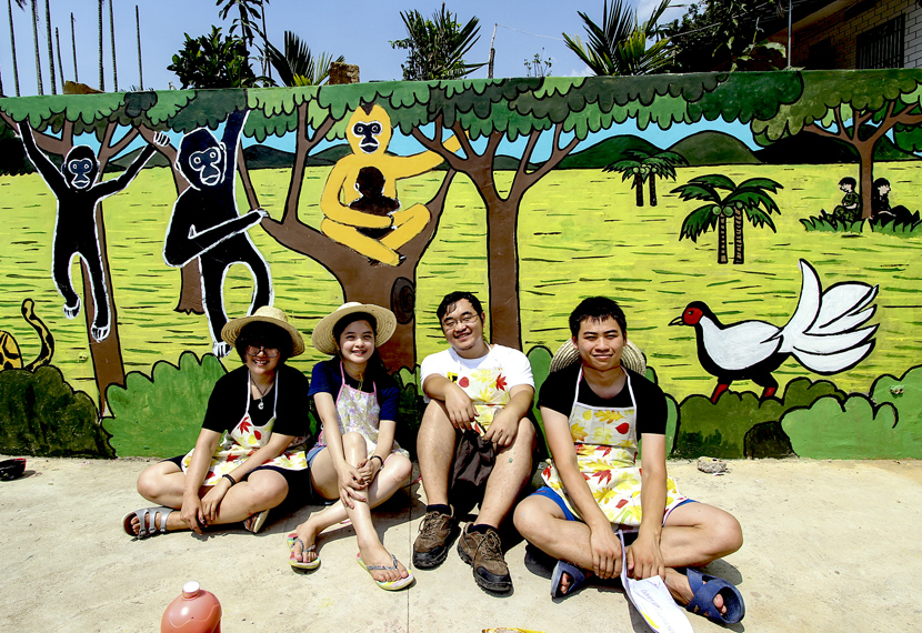 Students sit in front of a new mural of Hainan gibbons in the village of Miao Cun, Hainan province. The mural was painted as part of Kadoorie Farm's campaign to raise awareness about the Hainan gibbon. Courtesy of Kadoorie Farm & Botanic Garden