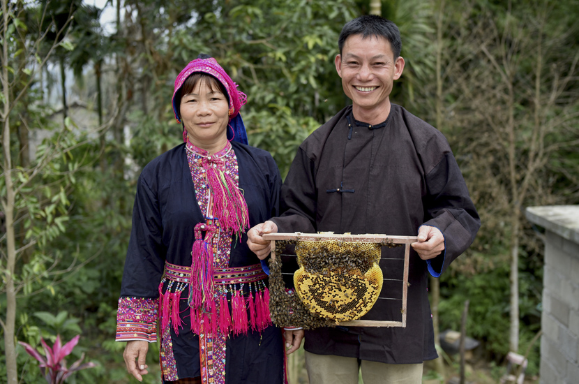 Li Wenyong, holding up a honeycomb from the hives, and his wife Xiumei pose for a photo near their home, in Qicha Town, Hainan province. Conservationists hope that honey may provide a sustainable source of income for people in Hainan. Courtesy of Kadoorie Farm & Botanic Garden
