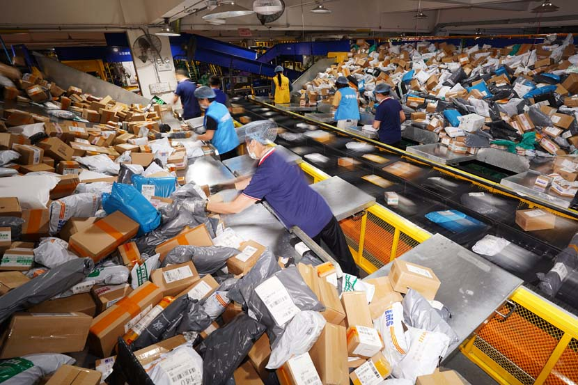 "Workers sort packages at a delivery center on ""Double Eleven,"" China's largest e-commerce shopping day, in Dongguan, Guangdong province, Nov. 11, 2020. People Visual"
