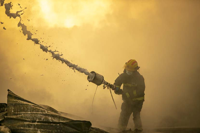 A fireman battles a blaze at a trash dump in Xiangyang, Hubei province, Nov. 11, 2020. People Visual