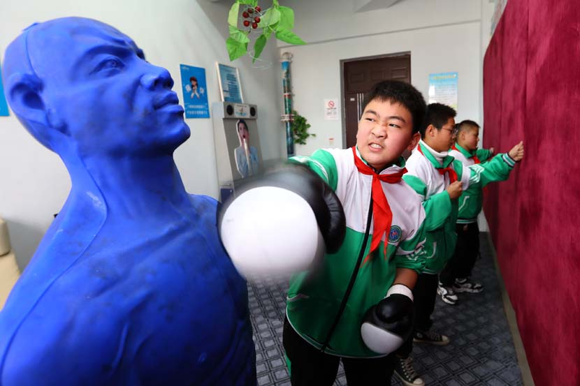 A boy works through his emotions by punching a dummy at a primary school counseling center in Huaibei, Anhui province, Nov. 15, 2020. People Visual