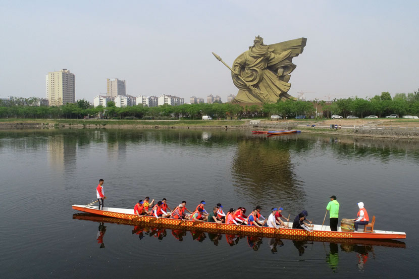 A team of rowers passes in front of a statue of Guan Yu in Jingzhou, Hubei province, May 3, 2019. Li Fuhua/People Visual