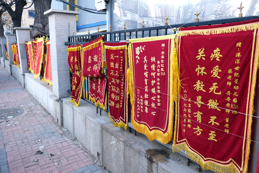 Ceremonial red banners on display outside a kindergarten in Shenyang, Liaoning province, 2019. Huang Jinkun/People Visual