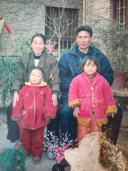 A family photo of Li Xinmei (front left) in Henan province, including her mother, father, and younger sister. Courtesy of Li Xinmei