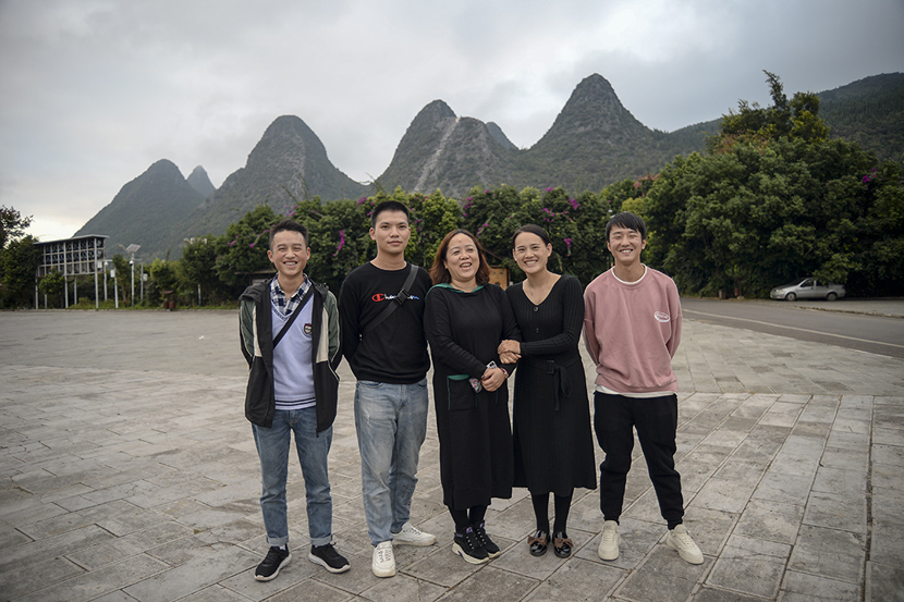 Huang Defeng (second from left), Wang Zhengzhi (center), and Li Xinmei (second from right) pose for a photo in Xingyi, Guizhou province, Oct. 27, 2020. Stephen Che/Guyu