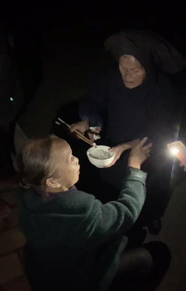 Dezliangz's mother feeds rice to her when she returns home in Qinglong County, Guizhou province, September 2020. Courtesy of Li Xinmei