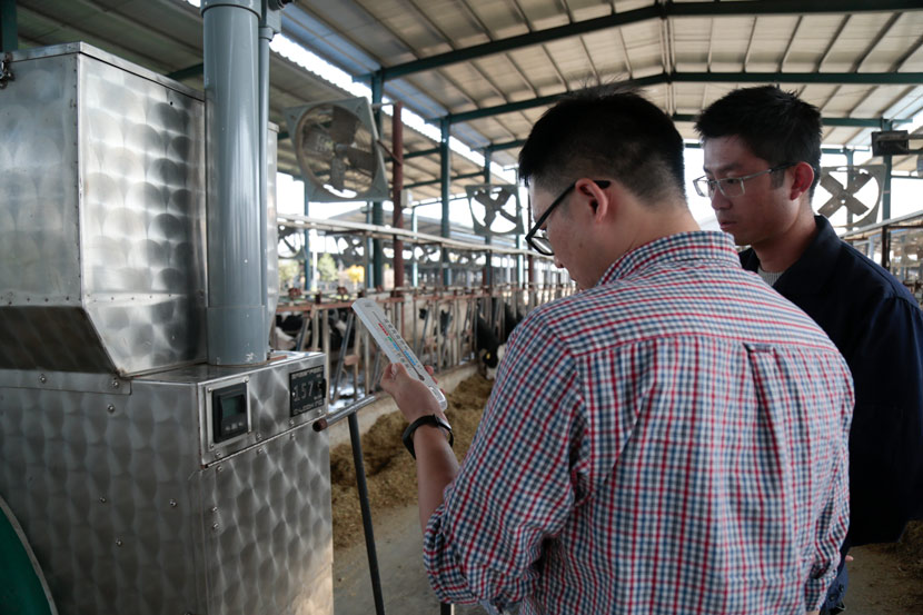 Dong Lifeng (left) and Jia Peng check the gauges on the Yinxiang Weiye dairy farm's gas flux quantification equipment in Heze, Shandong province, Nov. 6, 2020. Li You/Sixth Tone