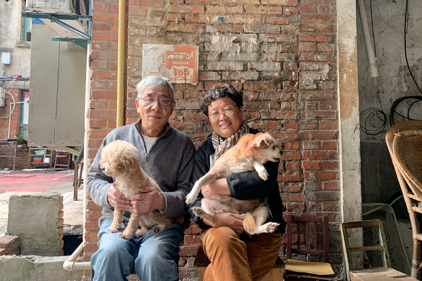 Lü Caiqiang and his wife pose for a photo in Pengpu New Village, Shanghai, Nov. 4, 2020. The couple raises two cats and two dogs. Wang Lianzhang/Sixth Tone
