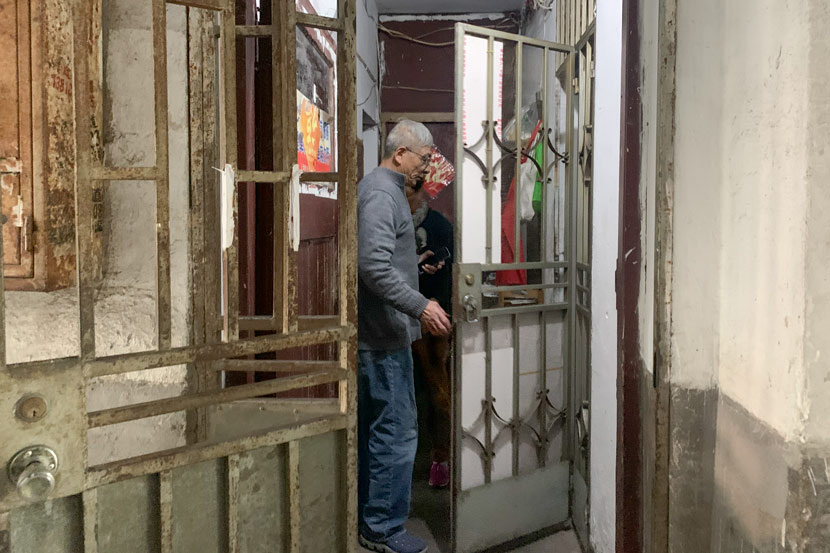 Lü Caiqiang opens the door to enter his 18-square-meter apartment in Pengpu New Village, Shanghai, Nov. 4, 2020. Wang Lianzhang/Sixth Tone