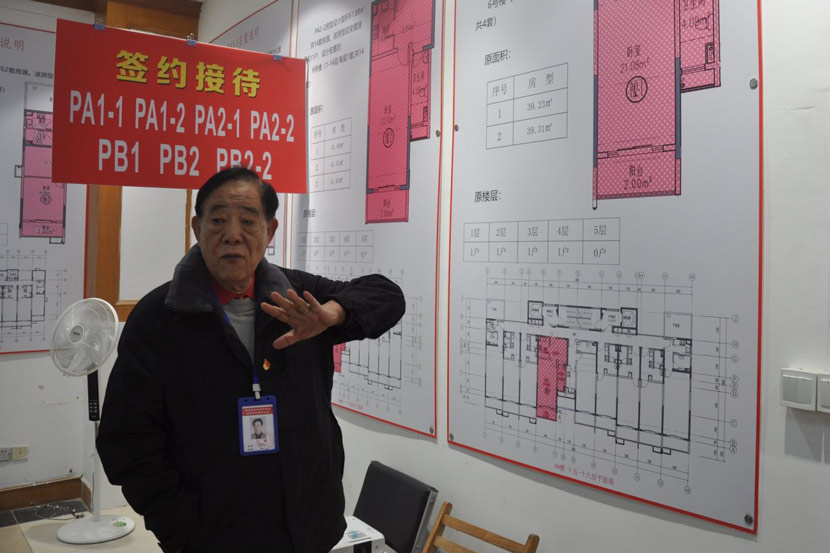 Xu Bingrong puts up plans on a wall for residents to see their new apartment house types, at a conference room in Pengpu New Village, Shanghai, Nov. 4, 2020. Zhang Shiyu for Sixth Tone