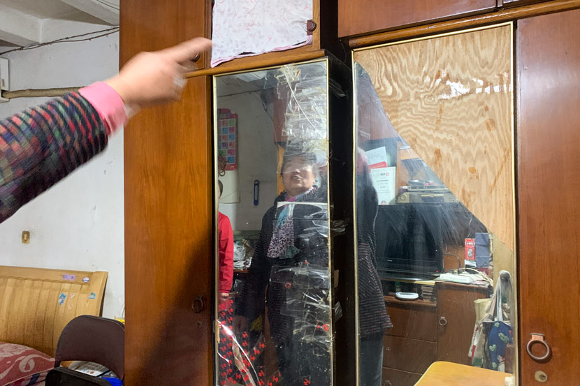 Wang Liyuan points to her closet's broken mirror in Pengpu New Village, Shanghai, Nov. 4, 2020. She dreams of a new one in her next apartment. Wang Lianzhang/Sixth Tone
