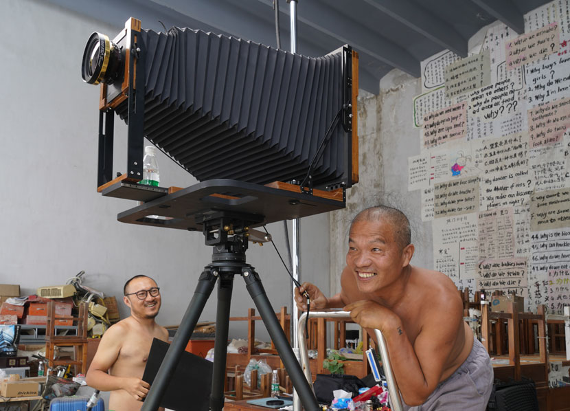 "Wang Qingsong (right) at work during the creation of ""Question A Brick Wall,"" Beijing, June 2020. His tattoo can be seen on his left wrist. Courtesy of Wang Qingsong"