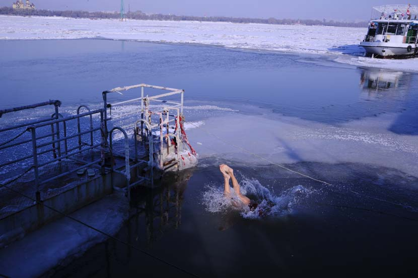 A winter swimmer leaps into the Songhua River in Harbin, Nov. 28, 2020. Wu Huiyuan/Sixth Tone
