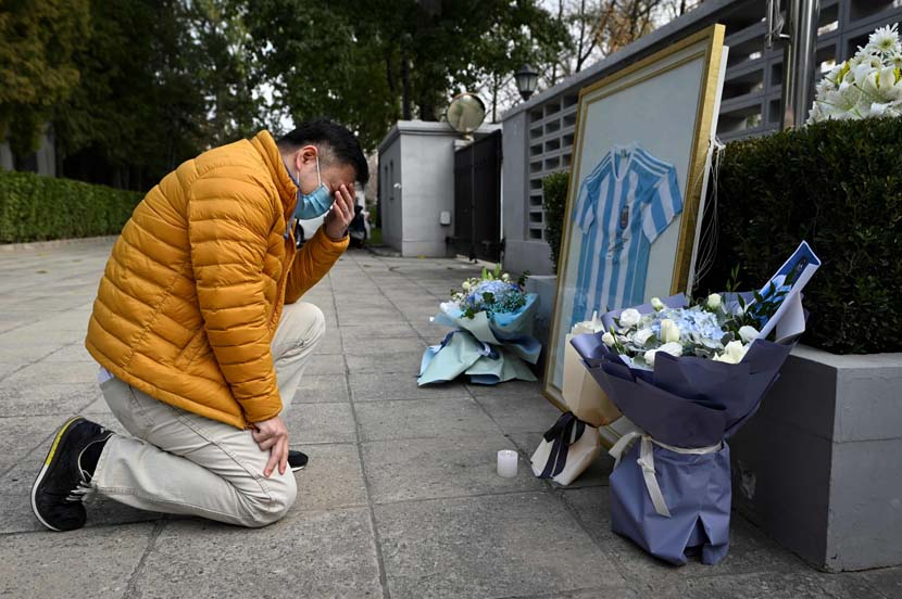 A fan pays his respects to the late Argentinian football legend Diego Maradona at the Embassy of Argentina in Beijing, Nov. 26, 2020. Wang Zhao/People Visual