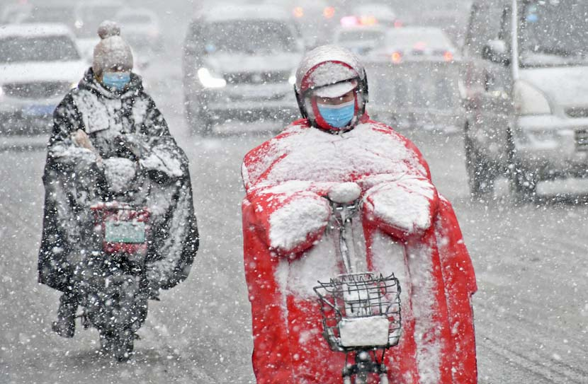 People ride electric scooters through snowfall, Yantai, Shandong province, Nov. 28, 2020. People Visual